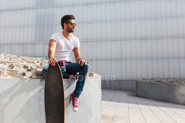 Trendy man with skateboard posing — Stock Photo