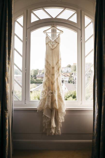 Wedding dress hanging on window — Stock Photo