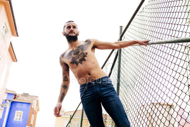 Sem camisa tatuado homem posando — Fotografia de Stock