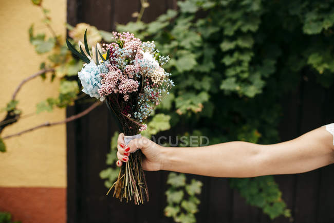 Hand with bunch of flowers — Stock Photo