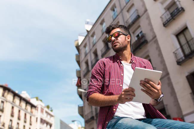 Jovem homem bonito em óculos de sol usando tablet em backgroun urbano — Fotografia de Stock