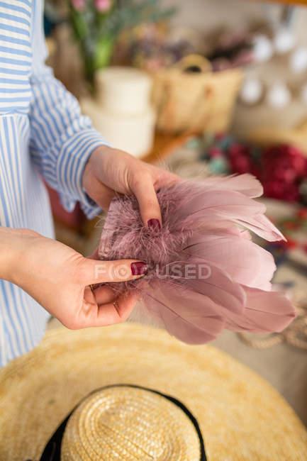 Mulher decorando um chapéu com flores — Fotografia de Stock