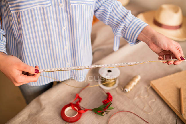 Woman measuring off ribbon for headband — Stock Photo