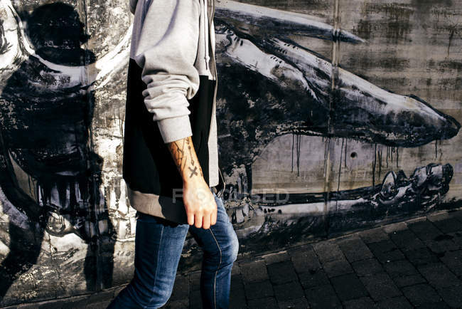 Crop tattooed man against wall with graffiti — Stock Photo