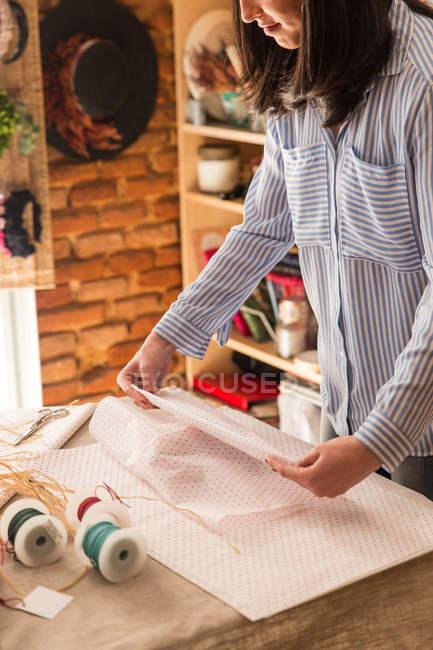 Woman wrapping box — Stock Photo