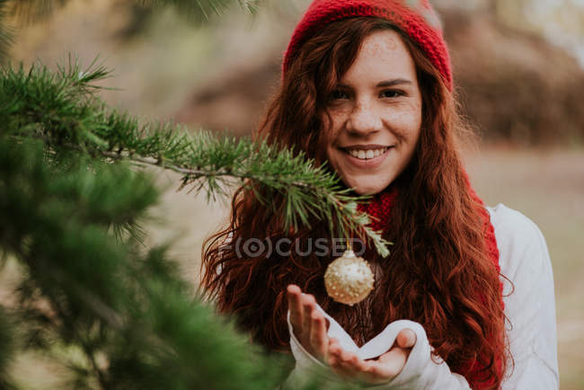 Portrait de sourire redhead girl holding mains sous Boule suspendue sur pin — Photo de stock