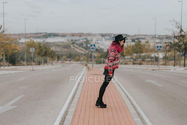 Girl bending at roadway — Stock Photo