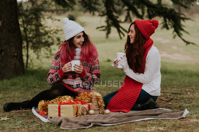 Two teen girlfriends sitting on festive picnic in forest — Stock Photo