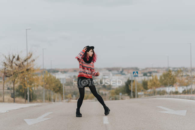 Girl with hat posing at urban roadway — Stock Photo