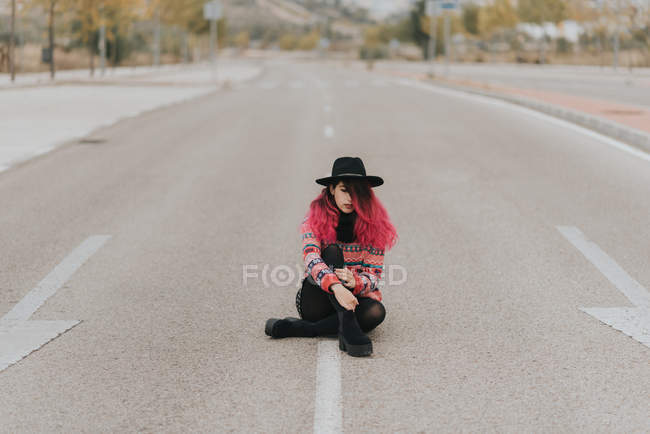 Girl sitting on roadway with crossed legs — Stock Photo