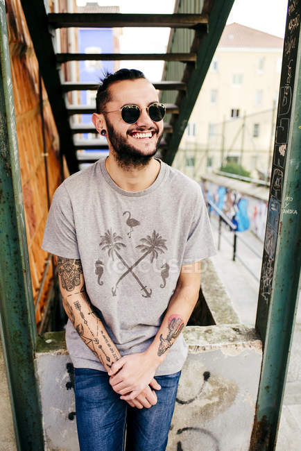 Smiling hipster man on urban background — Stock Photo