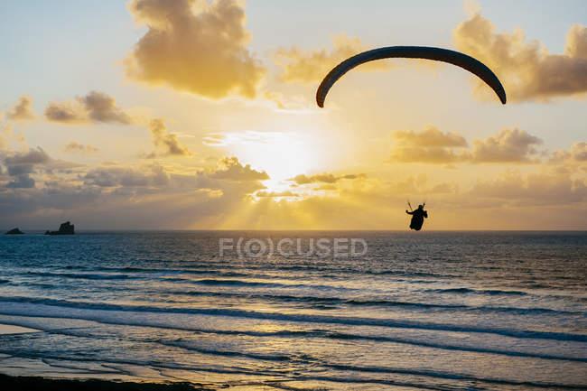 Silueta volando en paracaídas sobre el mar - foto de stock