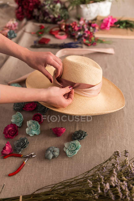 Crop person decorating hat with flowers — Stock Photo