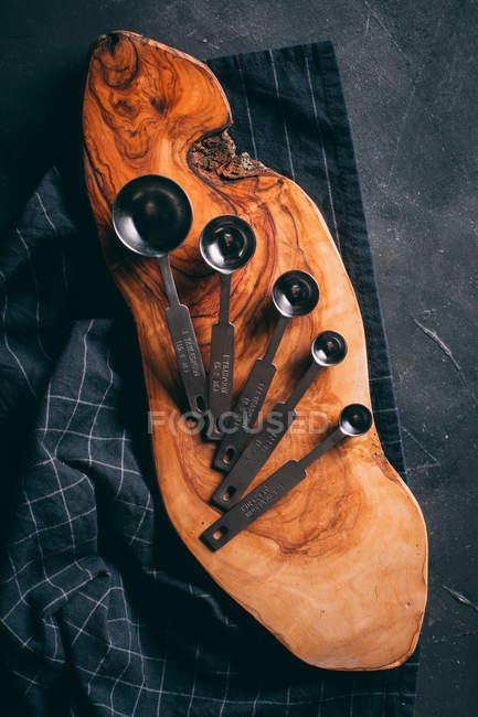 Cucharas de medir sobre tabla de madera - foto de stock