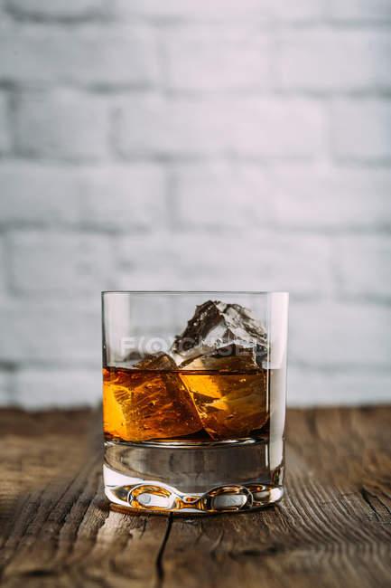 Стакан виски на деревянном столе — стоковое фото