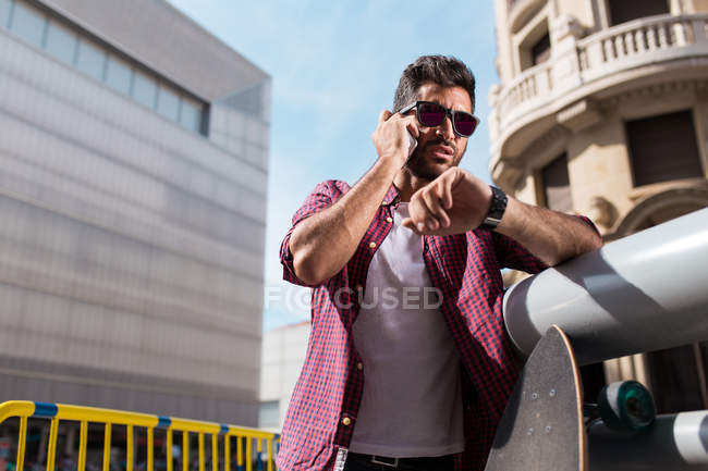 Handsome man with phone and longboard — Stock Photo