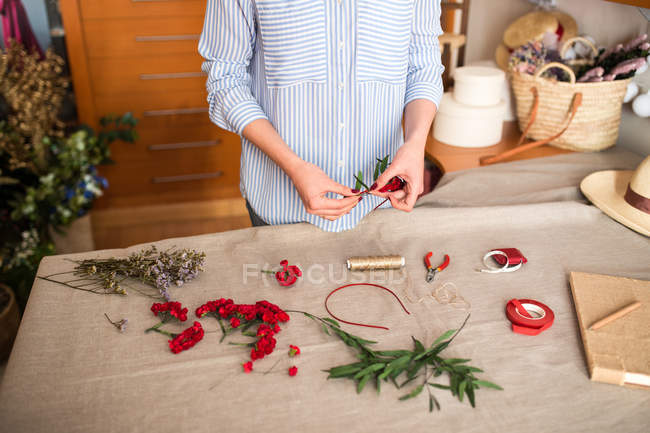 Crop person making headdress with flowers — Stock Photo