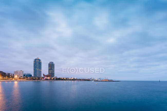 Serene landscape of coastline with skyscrapers against dusk sky — Stock Photo