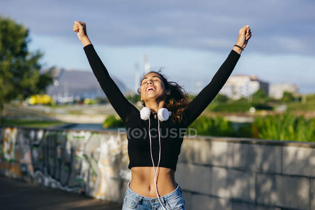 Happy girl with hands up on cityscape — Stock Photo