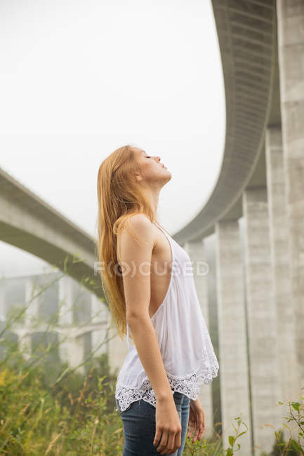Side view of young blonde woman stand in abandoned construction with eyes closed — Stock Photo