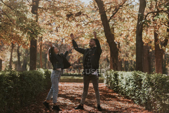 Cheerful couple throwing autumn foliage in air at park alley — Stock Photo
