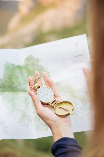 Ritagliare l'immagine della mano femminile che tiene la bussola d'oro sopra la mappa — Foto stock