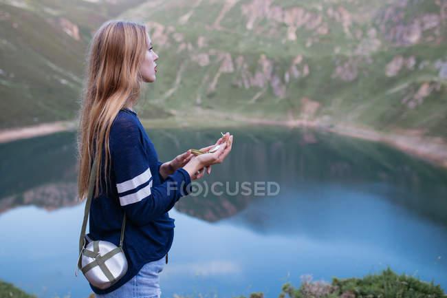 Ragazza che usando la bussola nel lago della montagna — Foto stock