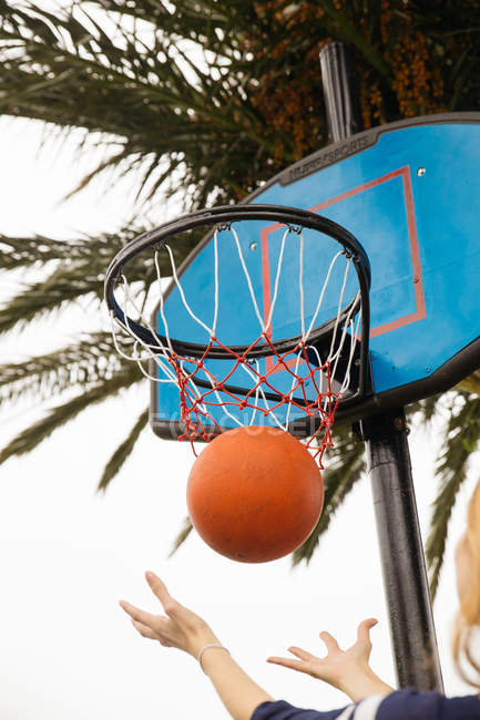 Low angle view of basketball falling through hoop — Stock Photo