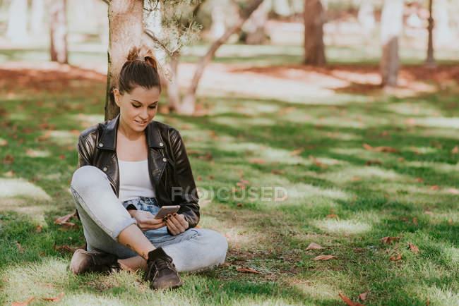 Porträt eines lächelnden Mädchens, das im Gras sitzt und auf seinem Smartphone surft — Stockfoto