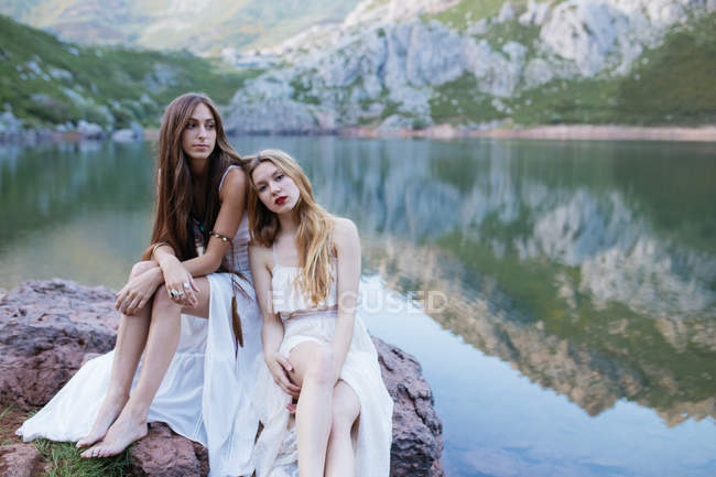 Two girls in white dresses sitting on boulder — Stock Photo