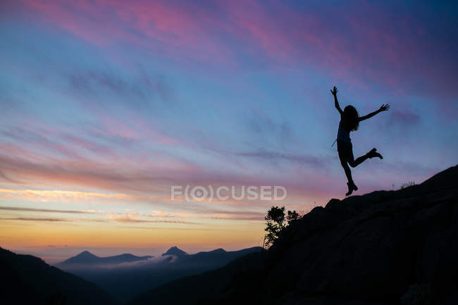 Silhouette of girl jumping on cliff — Stock Photo