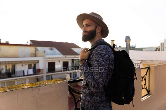 Stylish male with backpack on balcony — Stock Photo