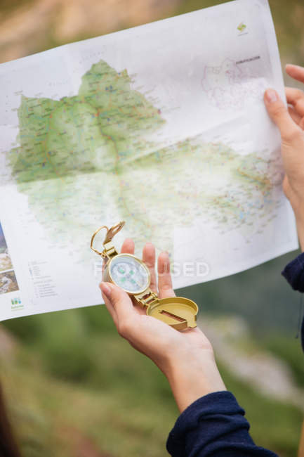Female hand with compass over map — Stock Photo