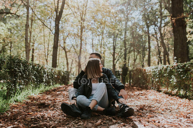 Young couple sitting on ground at park alley — Stock Photo