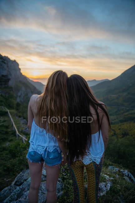 Задній вид дві жінки, дивлячись на захід сонця на гори — стокове фото