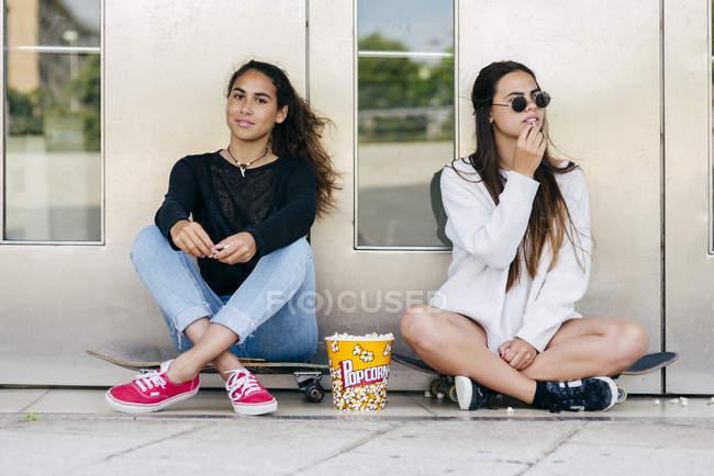 Стильные подростки с попкорном на коньках — стоковое фото