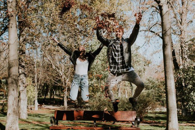 Happy couple in midair while throwing dry leaves up high — Stock Photo
