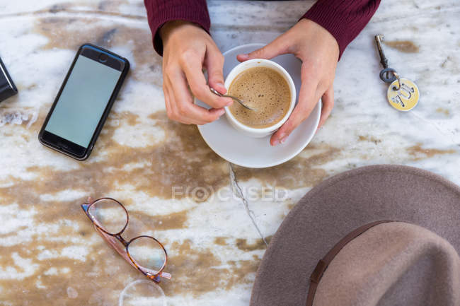 Crop shot from above of female holding phone and coffee on table — Stock Photo