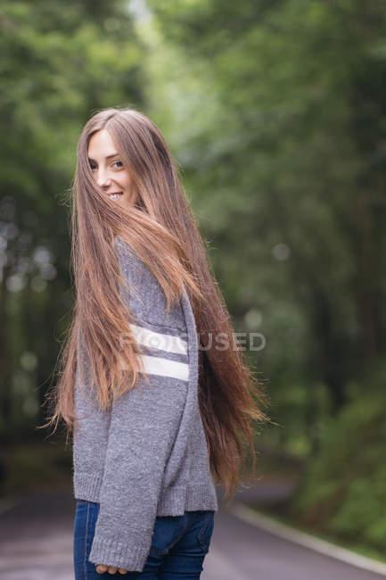 Porträt eines brünetten Mädchens, das auf der Straße geht und über die Schulter in die Kamera schaut — Stockfoto