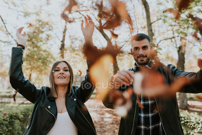 Portrait of young people throwing dry yellow leaves at camera — Stock Photo