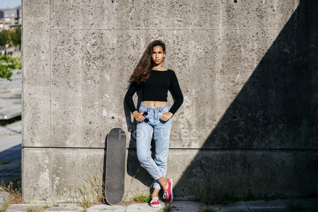 Стильная девушка со скейтом — стоковое фото