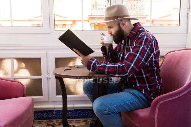 Young male with book at cafe — Stock Photo