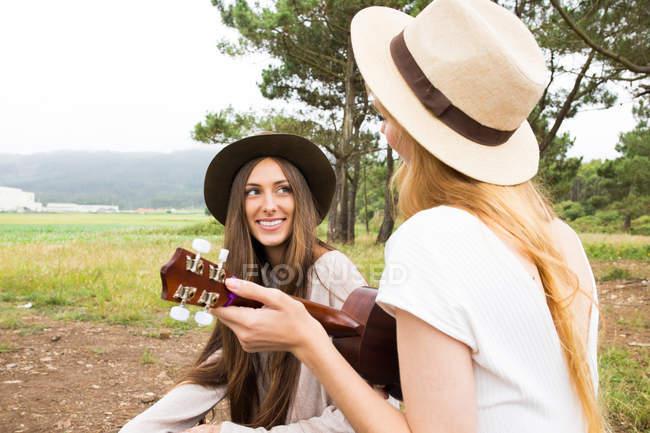 Girl playing ukulele in front of brunette girl — Stock Photo