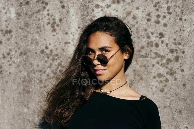 Trendy girl looking over sunglasses — Stock Photo