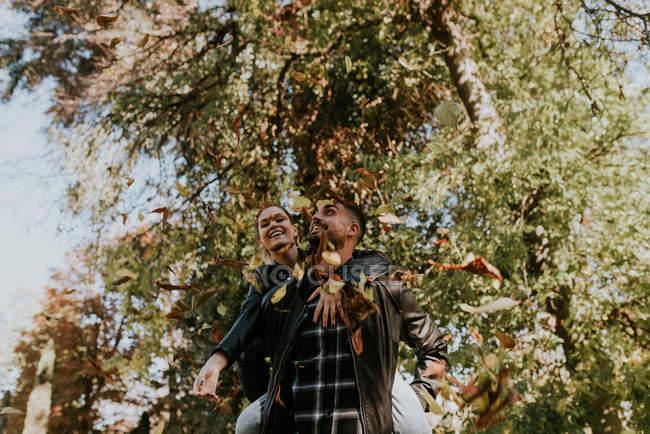Hombre joven montando chica en la espalda en el parque de otoño - foto de stock