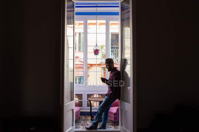Uomo in cappello in piedi sulla porta — Foto stock