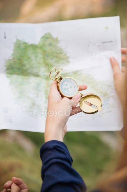 Mano femminile con bussola e mappa — Foto stock