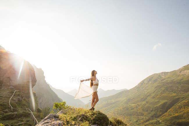 Vista lateral da jovem morena desfrutando de liberdade contra a paisagem da montanha à luz do sol — Fotografia de Stock