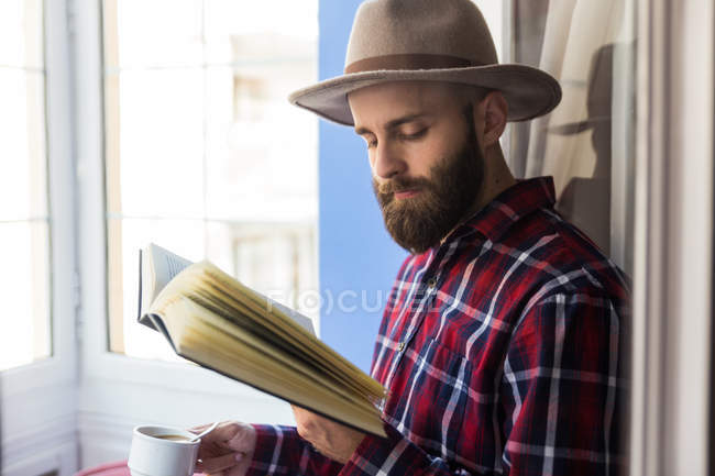 Male with book drinking coffee — Stock Photo