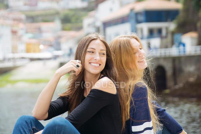 Retrato de alegres melhores amigas sentado de costas na rua — Fotografia de Stock